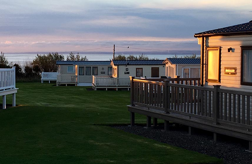 Silverdyke caravan park at sunset with the sea in the background