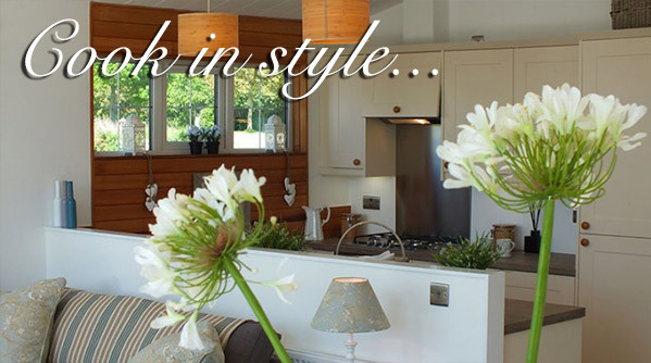 A kitchen in a luxury lodge at Silverdyke Park with text saying cook in style