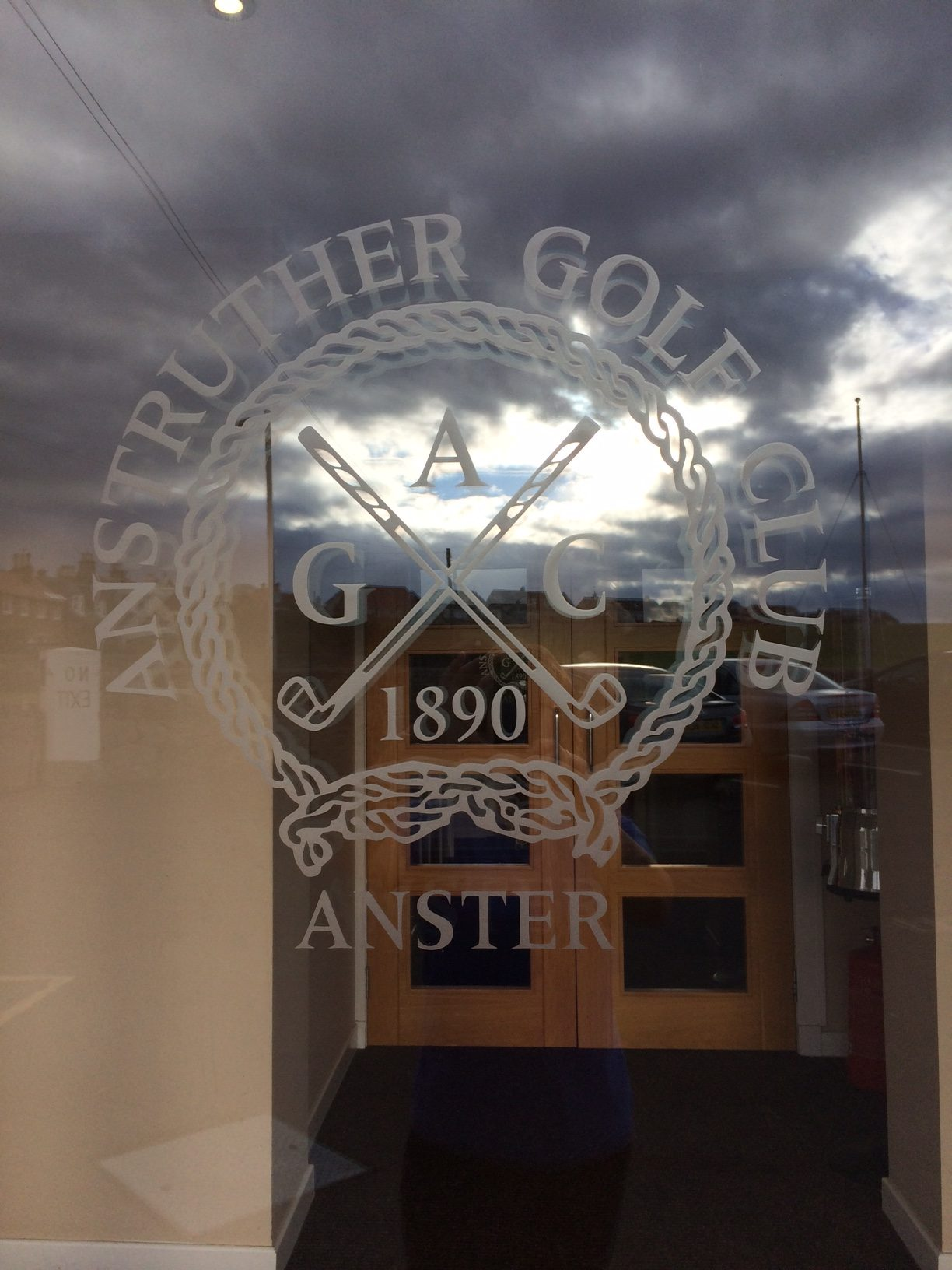 Anstruther golf club logo on the glass clubhouse door
