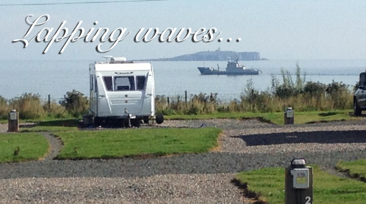 Caravan with sea behind it and a boat at Silverdyke Park