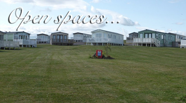 Exterior of holiday homes in an open space at Silverdyke Park with text saying open spaces