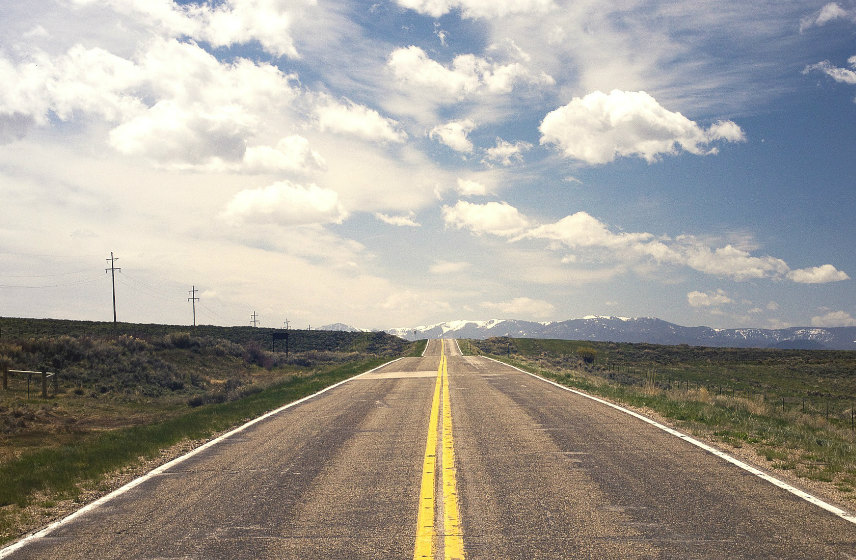 Long open road with mountains in the background