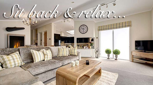 A luxury living area in a luxury lodge at Silverdyke Park with text saying sit back and relax