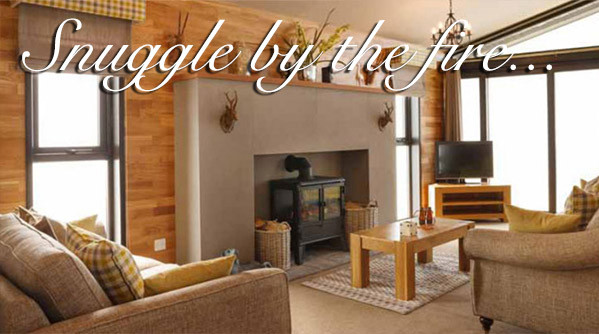 Sitting area around a stove fireplace in a lodge at Silverdyke Park with text saying snuggle by the fire