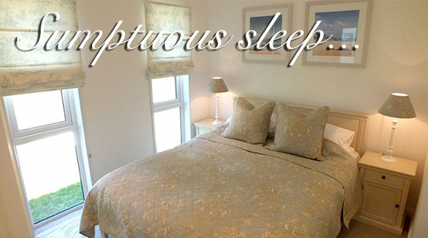 A double bed in a luxury lodge at Silverdyke Park with text saying sumptuous sleep